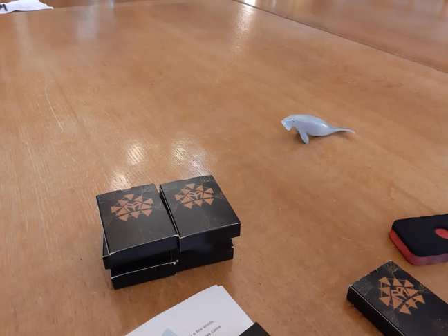 a plastic model of a dugong and packs of playing cards on a large wooden meeting table